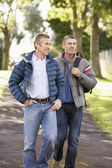 Two Male Friends Walking Outdoors In Autumn Park Together — Stok fotoğraf