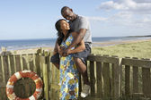 Romantic Young Couple Standing By Wooden Fence Of Beach Hut Amon — Foto Stock