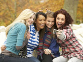 Group Of Four Teenage Girls Taking Picture With Camera Sitting O — Stock Photo