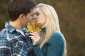 Romantic Teenage Couple Kissing Behind Autumn Leaf — Stock Photo