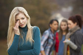 Upset Teenage Girl With Friends Gossiping In Background — Stock Photo