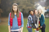 Upset Teenage Girl With Friends Gossiping In Background — Stok fotoğraf