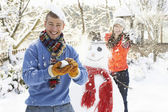 Young Couple Having Snowball Fight In Garden — Stock Photo