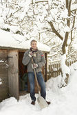 Middle Aged Man Clearing Snow From Path To Wooden Store — Stok fotoğraf