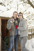 Young Couple Clearing Snow From Path To Wooden Store — Стоковое фото