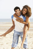 Romantic Young Couple Having Piggyback Fun On Beach — Stock Photo