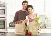 Young Couple Unpacking Shopping In Modern Kitchen — Stok fotoğraf