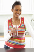 Young Woman Drinking Glass Of Water In Modern Kitchen — Stock Photo