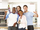 Group Of Young Friends Enjoying Drink In Modern Kitchen — Stock Photo