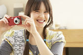 Young Woman Taking Photograph On Digital Camera At Home — Stock Photo