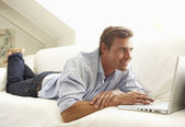 Hombre usando portátil relajante — Foto de Stock