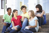 Group Of Teenage Friends Sitting On College Steps Outside — Stockfoto