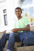 Male Teenage Student Sitting Outside On College Steps — Stockfoto
