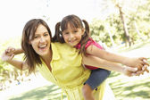 Mother Giving Daughter Ride On Back In Park — Stockfoto