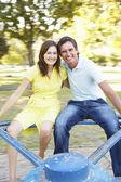 Mladý pár, na kruhovém objezdu v parku — Stock fotografie