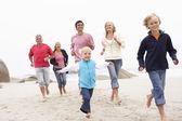 Familia de tres generaciones corriendo juntos en la playa de invierno — Foto de Stock