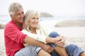 Senior Couple On Holiday Sitting On Winter Beach — Stock Photo