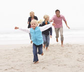 Young Family Running Along Winter Beach — Stock Photo