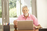 Senior hombre uso portátil en casa — Foto de Stock