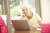 Mujer senior uso portátil en casa — Foto de Stock