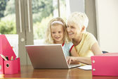 Granddaughter And Grandmother Using Laptop At Home — Stock Photo