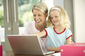 Mother And Daughter Using Laptop At Home — Stockfoto