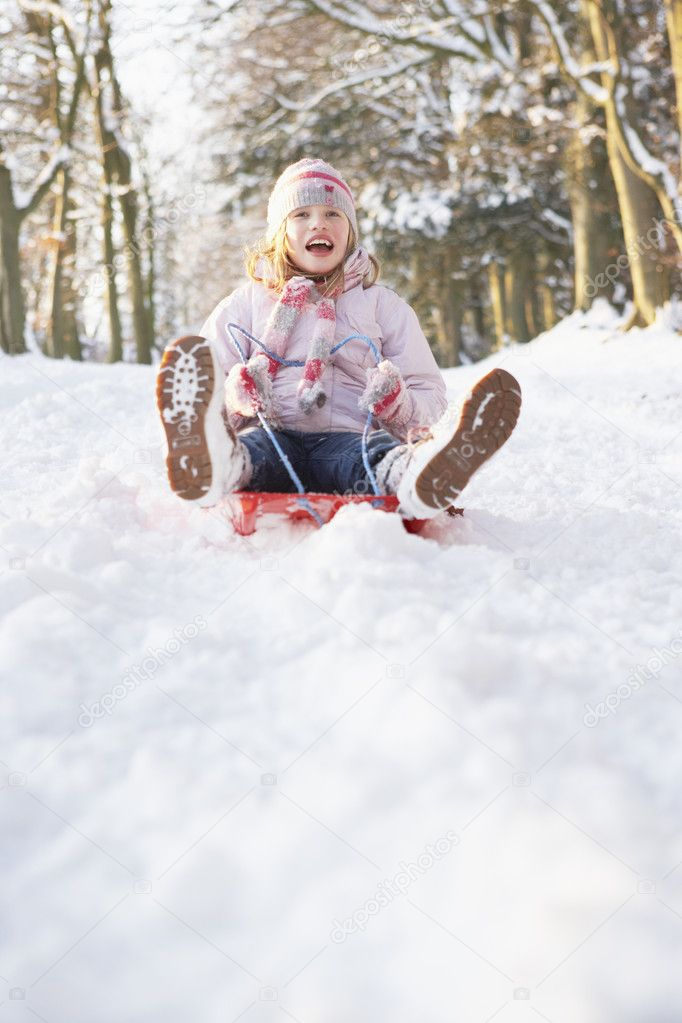 Girl Sledging Through Snowy Woodland  Stock Photo #4836239