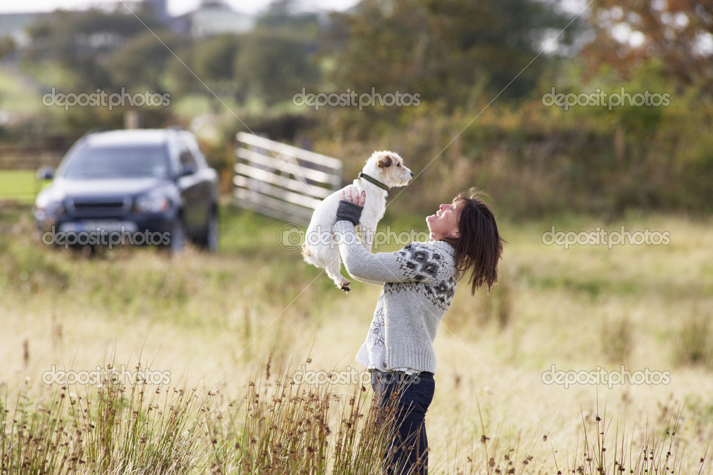 Young Woman Outdoors In Autumn Landscape Holding Dog — Stock Photo #4836557
