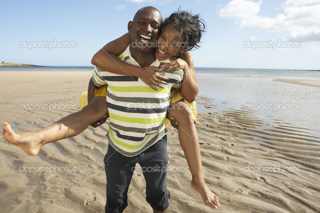Young Man Giving Woman Piggyback Along Shoreline Of Beach — Stock Photo #4836676