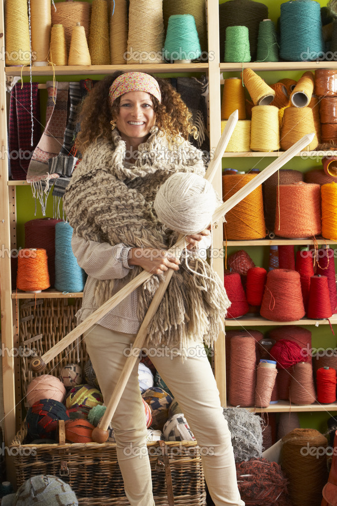 Woman Wearing Knitted Scarf Standing In Front Of Yarn Display Ho — Stock Photo #4837191