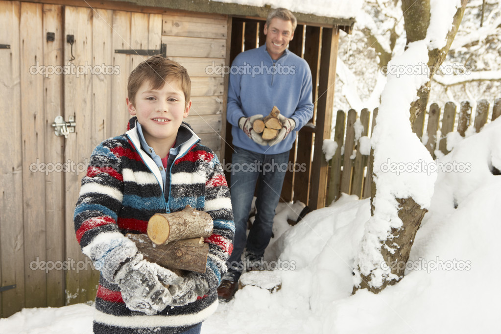Father And Son Collecting Logs From Wooden Store In Snow — Stock Photo #4837564
