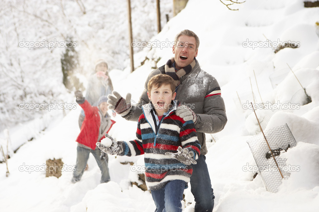 Family Having Snowball Fight In Snowy Landscape — Stock Photo #4837568