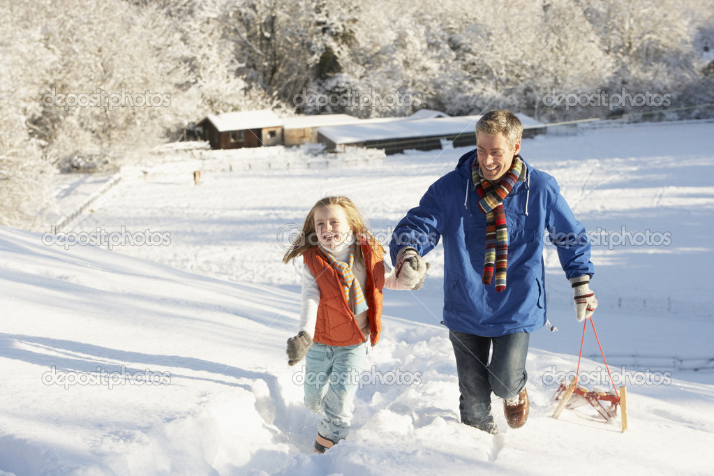 Father And Daughter Pulling Sledge Up Snowy Hill — Stock Photo #4837572