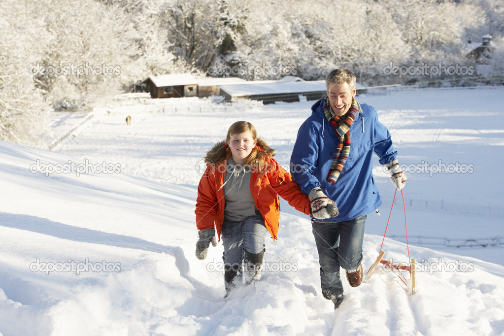 Father And Son Pulling Sledge Up Snowy Hill  Stock Photo #4837574