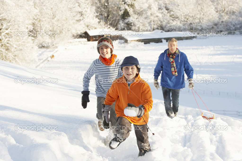 Father And Children Pulling Sledge Up Snowy Hill — Stock Photo #4837577