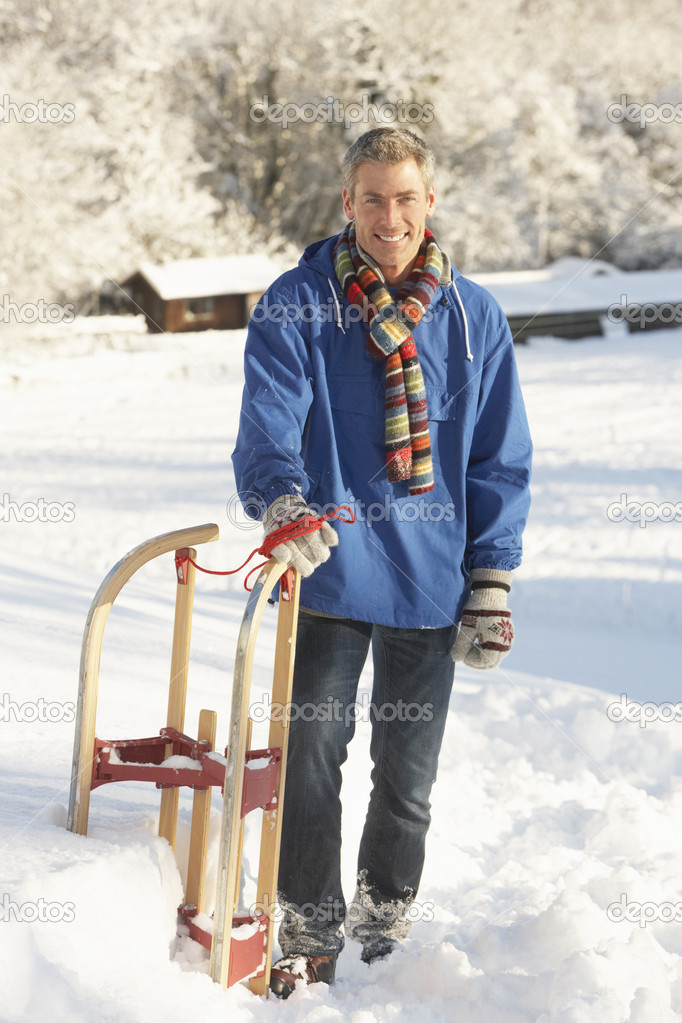 Middle Aged Man Standing In Snowy Landscape Holding Sledge  Stock Photo #4837580