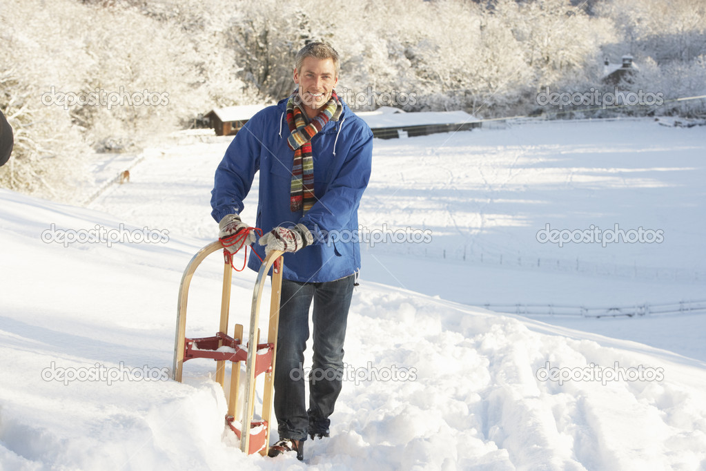 Middle Aged Man Standing In Snowy Landscape Holding Sledge — Stock Photo #4837581