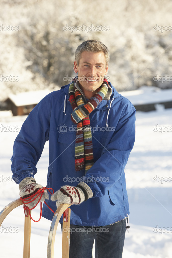 Middle Aged Man Standing In Snowy Landscape Holding Sledge — Stock Photo #4837582