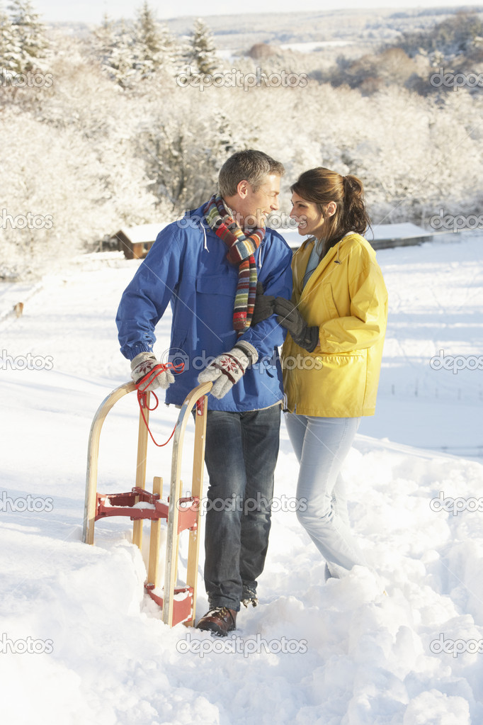 Young Couple Standing In Snowy Landscape Holding Sledge — Stock Photo #4837584