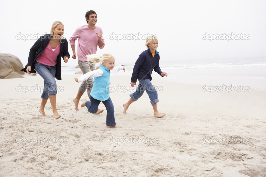 Young Family Running Along Winter Beach — Stock Photo #4839496
