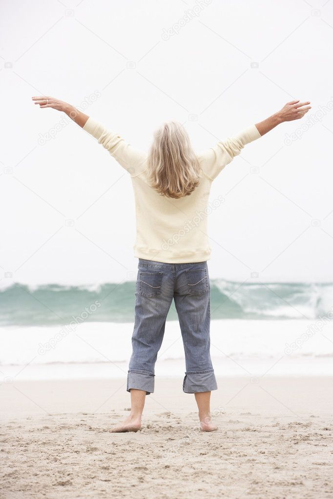 Senior Woman With Arms Outstretched On Winter Beach — Stock Photo #4839555