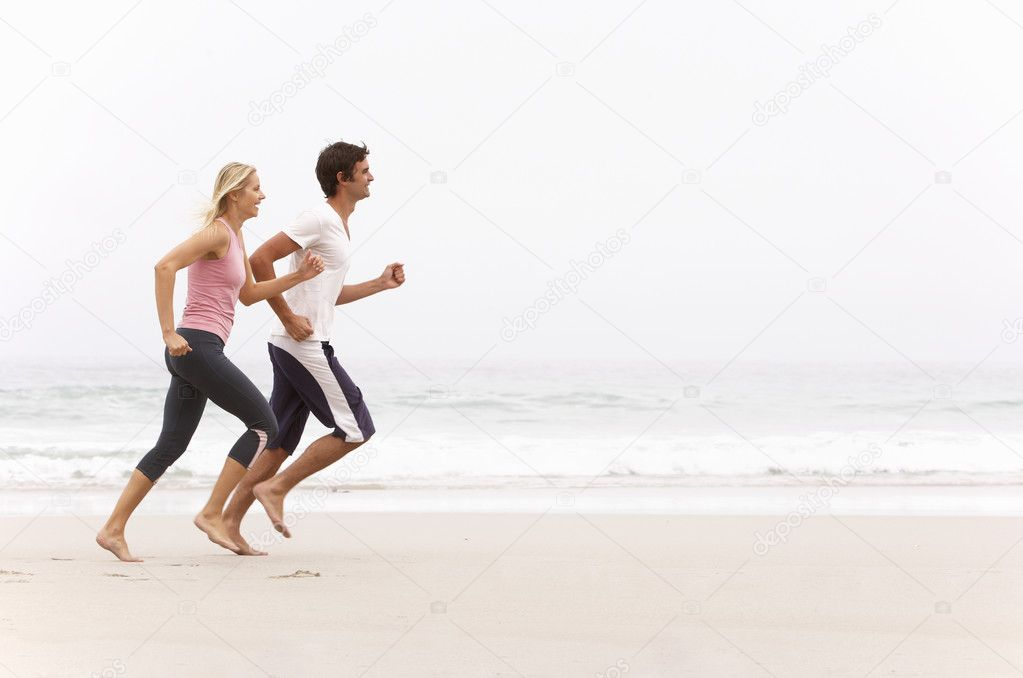 Young Couple Running Along Winter Beach — Stock Photo #4839570