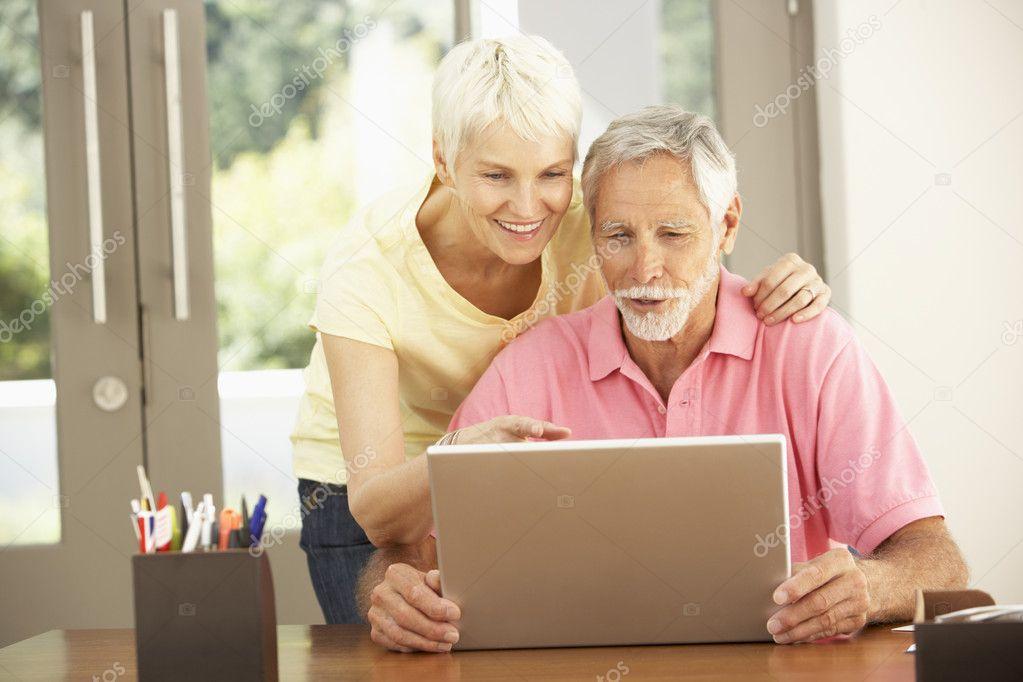 couple de personnes g es l 39 aide d 39 ordinateur portable la maison photographie. Black Bedroom Furniture Sets. Home Design Ideas