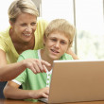 mère et fils adolescent à l'aide d'ordinateur portable à la maison — Photo