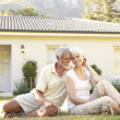 Senior Couple sitting Outside Dream Home — Stock Photo #4840209