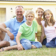 Family Sitting Outside Dream Home - Foto Stock