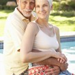 Senior Couple Relaxing By Pool In Garden — Stock Photo
