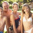 Young Family Relaxing By Pool In Garden — Stock Photo