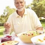 Senior Man Enjoying Meal In Garden — Stock Photo #4840234