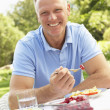 Man Enjoying Meal In Garden — Stock Photo #4840243